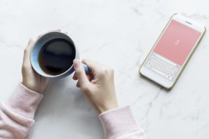 Hands holding coffee cup on marble desk next to phone with white smiley face on the screen over a pink background.